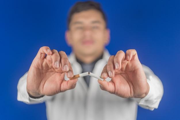 Smettere di fumare il concetto di sigarette. ritratto di medico che tiene la sigaretta rotta in mano. smettere di fumare sigarette. abbandona la cattiva abitudine, concetto di assistenza sanitaria. vietato fumare.