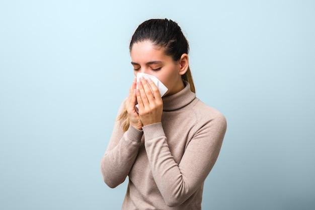 Smetti di diffondere coronavirus. giovane donna malata con mosca o virus che starnutisce e tossisce in una maschera o un tovagliolo che sembra molto senza speranza