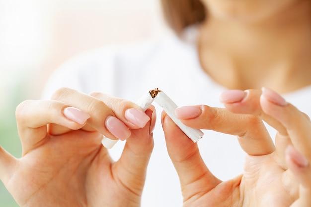 Smetti di fumare, primo piano di donna con una sigaretta rotta