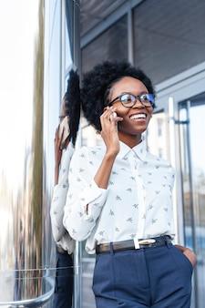Smile di angolo basso femminile parlando al telefono