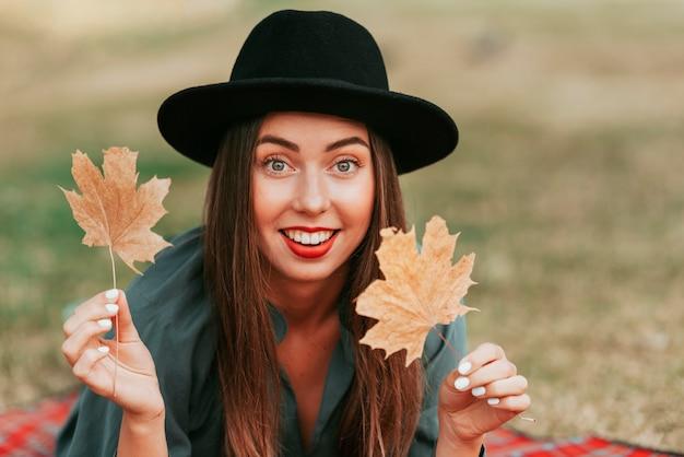 Smiley donna che indossa un cappello mentre si sta su una coperta