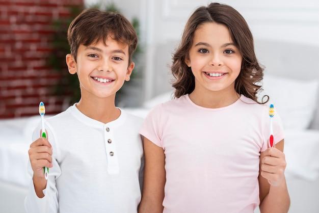 Smiley fratelli a casa tenendo lo spazzolino da denti