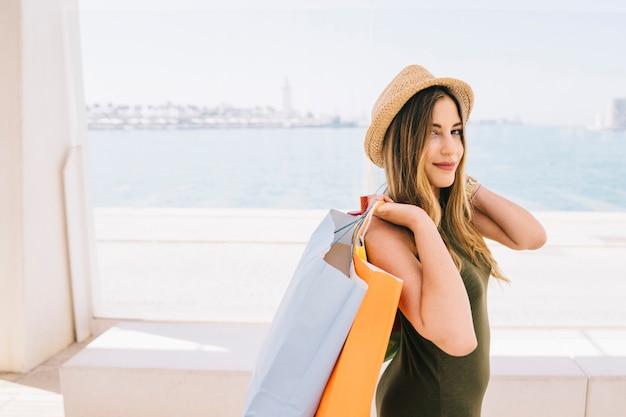 Smiley giovane donna in posa con borse della spesa e cappello