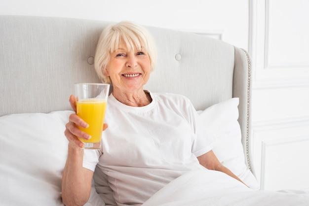 Smiley senior in possesso di un bicchiere con succo