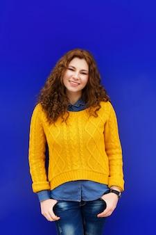 Smilig della ragazza del giovane brunette grazioso di modo in maglione giallo