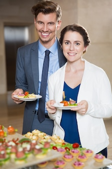 Smiling business people con spuntini a buffet