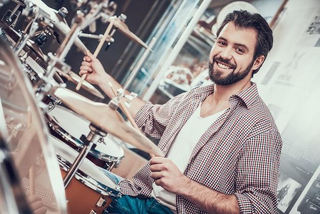 Smilling uomo barbuto in camicia gioca sul set di batteria.