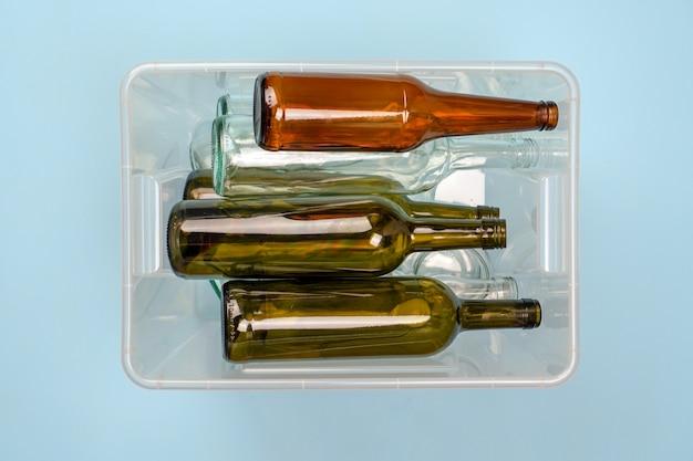 Smistamento dei rifiuti. contenitore con bottiglie di vetro di vino e birra su sfondo blu.
