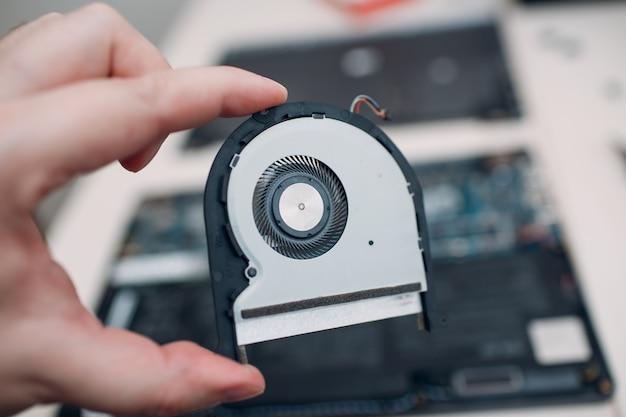 Smontare e riparare il laptop. servizio, sistema di raffreddamento di ricambio, dispositivo di raffreddamento in mano.