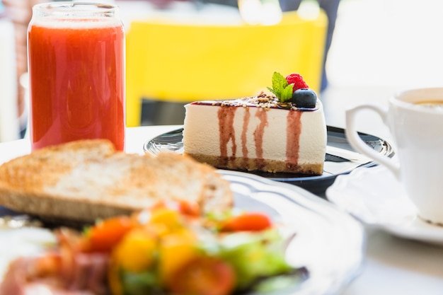 Smoothie; cheesecake ai frutti di bosco e colazione sul tavolo