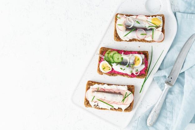 Smorrebrod salato, set di panini tradizionali danesi. pane nero di segale con acciuga, barbabietola rossa