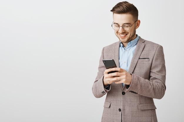 Sms di successo giovane imprenditore maschio, messaggistica con lo smartphone