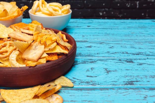 Snack alla birra come cracker, patatine, biscotti su una superficie di legno