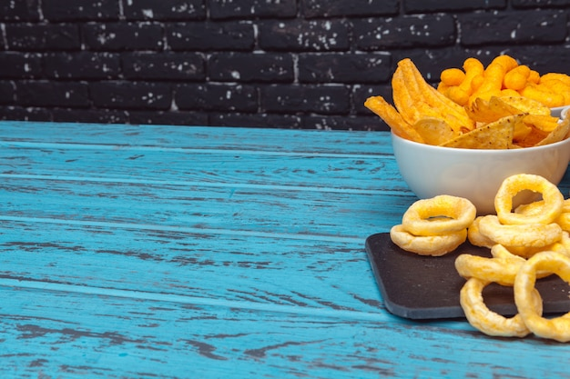 Snack alla birra come cracker, patatine, biscotti su uno sfondo di superficie in legno