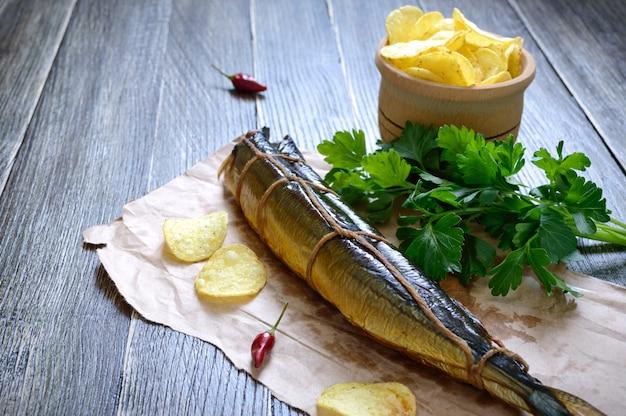 Snack alla birra. pesce affumicato, patatine fritte su un tavolo di legno. luccio sauro artigianale affumicato.