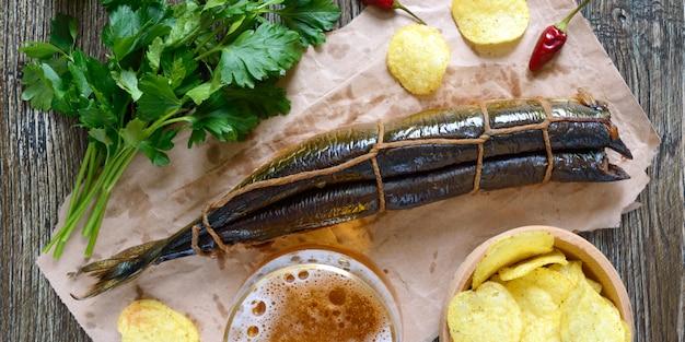 Snack alla birra. pesce affumicato, patatine fritte, un bicchiere di birra chiara su un tavolo di legno.