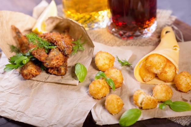 Snack alla birra. polpette fritte fritte del formaggio e del pesce con il limone e le verdure. snack a diverse birre.