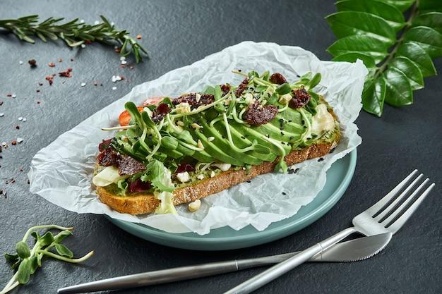 Snack alla moda da strada. gustoso brindisi con avocado su carta artigianale su una superficie nera