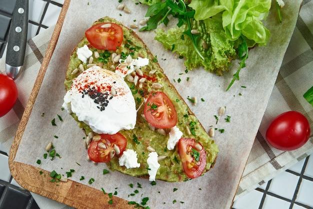 Snack alla moda da strada. gustoso brindisi di avocado su carta artigianale su un tavolo bianco. nutrizione vegetariana. vista da vicino