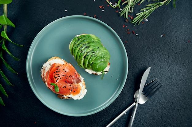 Snack alla moda. gustoso sandwich toast con salmone e avocado su carta artigianale su un tavolo nero. vista dall'alto. scopri il cibo con lo spazio della copia. frutti di mare