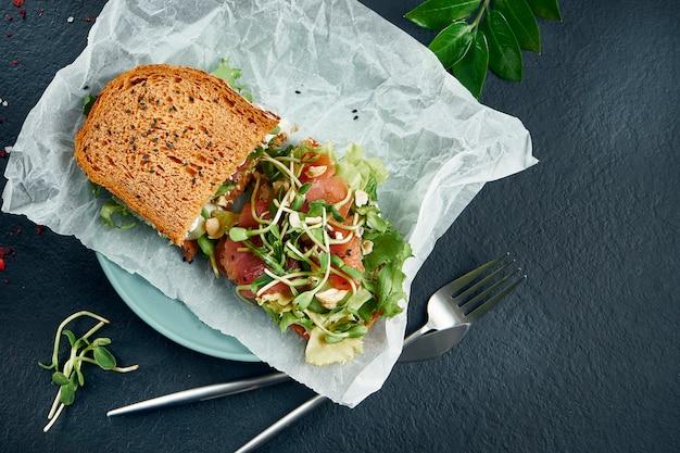 Snack alla moda. gustoso toast con salmone e microgreen su carta artigianale su un tavolo nero. vista dall'alto. scopri il cibo con lo spazio della copia. frutti di mare