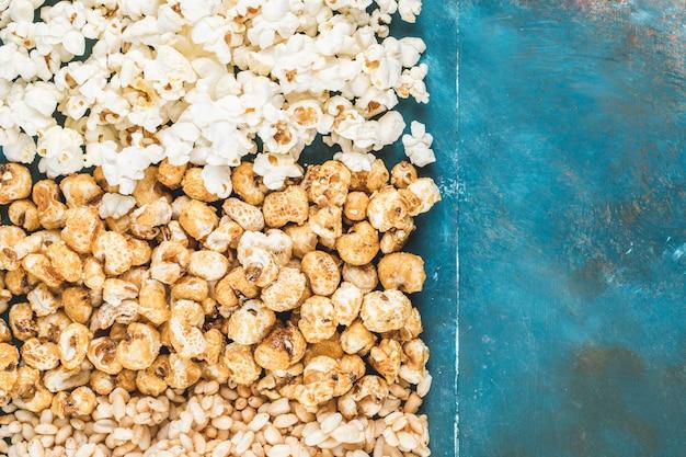 Snack di popcorn, mais caramellato e mais su sfondo blu