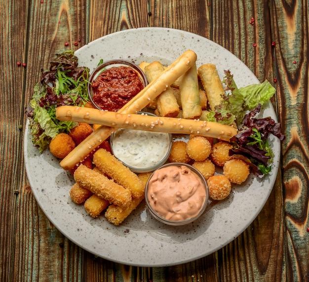 Snack fritti con due diverse salse sul nero