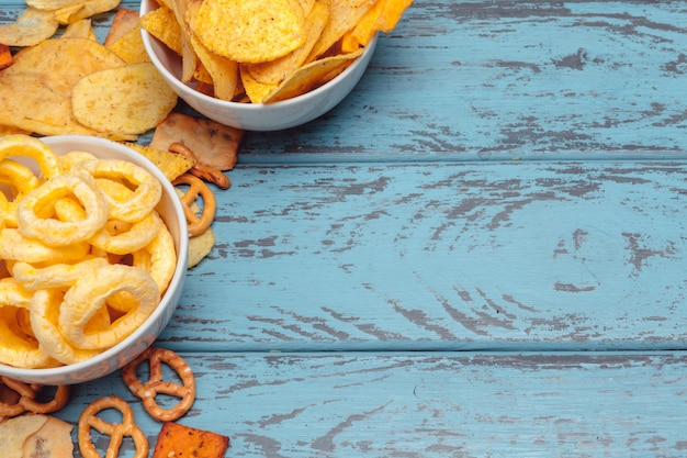 Snack salati. ciambelline salate, patatine fritte, cracker su fondo di legno. prodotti malsani