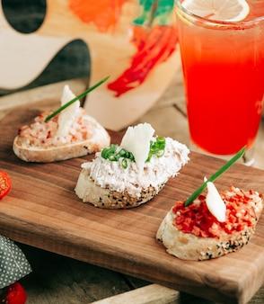 Snack sandwich sul tavolo con cocktail rosso