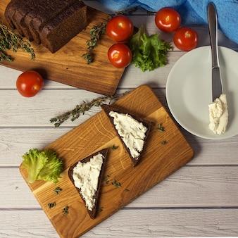 Snack sani panini con formaggio di capra, insalata, pomodorini. vista dall'alto in stile instagram