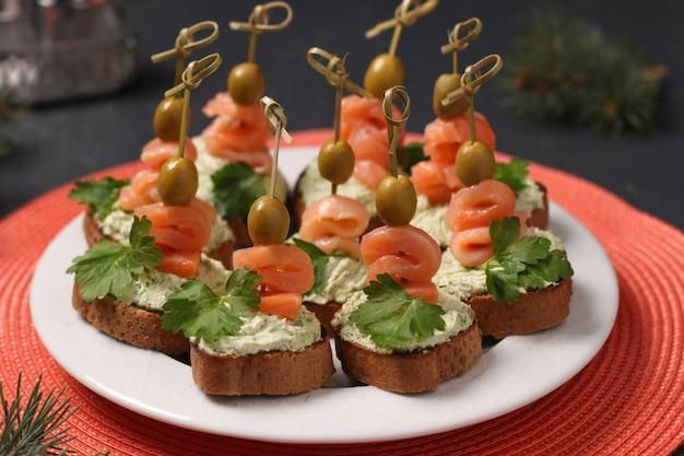 Snack su un tavolo festivo - tartine con salmone, crema di formaggio, olive e avocado