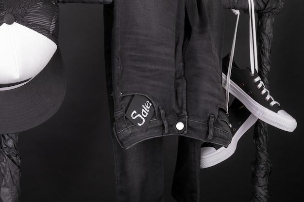Snaekers in bianco e nero, berretto e pantaloni, jeans appesi su appendiabiti.