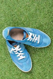 Sneaker blu alla moda di moda sul campo di erba