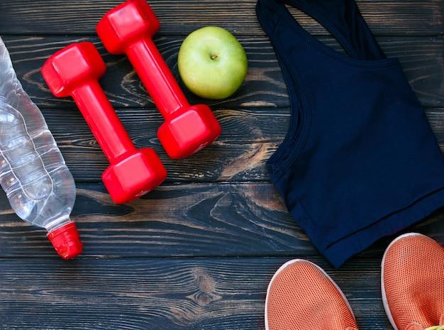 Sneaker sportive, manubri, acqua potabile pulita