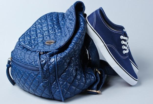 Sneakers alla moda, tavolo in pelle con portafoglio grigio.
