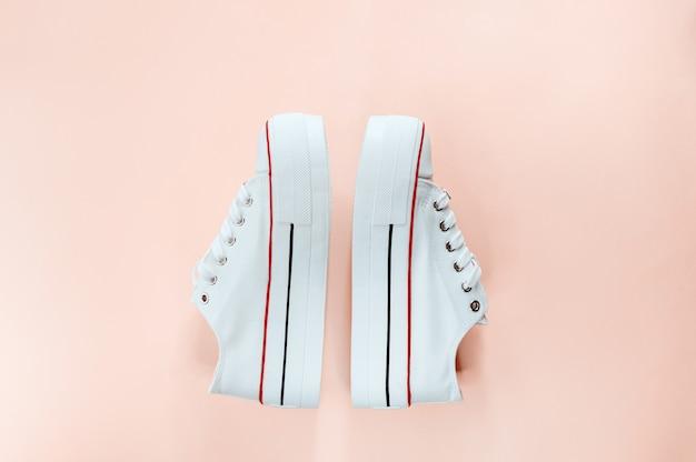 Sneakers bianche alla moda bianche su pesca cremosa