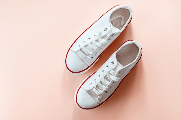 Sneakers bianche alla moda bianche su sfondo color crema. vista piana, vista dall'alto. posto per il testo. composizione in stile minimalista.