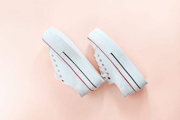 Sneakers bianche alla moda bianche su sfondo color crema