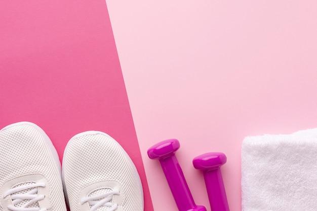 Sneakers bianche e pesi asciugamano rosa con spazio di copia