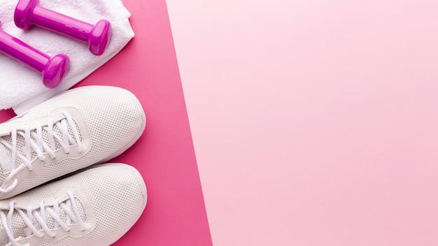 Sneakers bianche e pesi rosa con spazio di copia