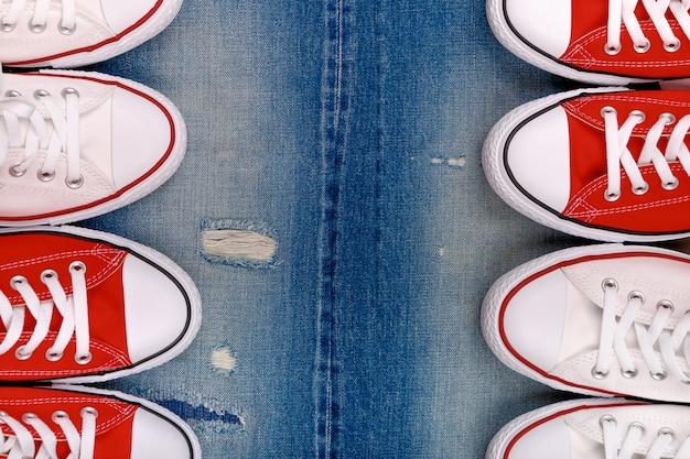 Sneakers bianche e rosse su un denim strappato