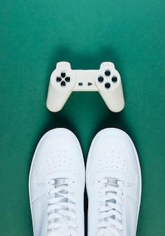 Sneakers bianche, gamepad sul tavolo verde.