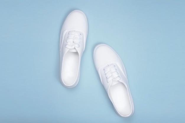 Sneakers bianche su fondo blu, piatto. scarpa di tendenza moda, negozio di scarpe concept