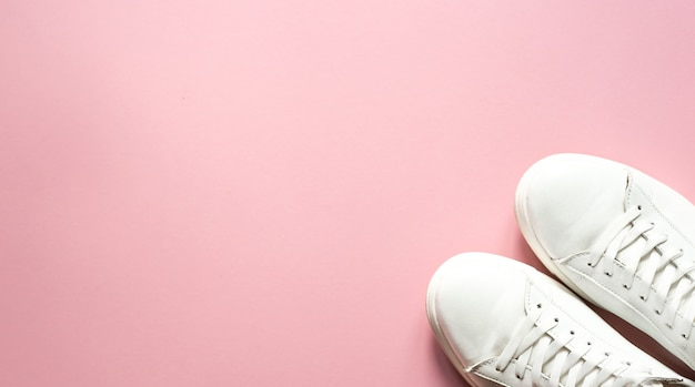Sneakers bianche su sfondo rosa pastello con vista dall'alto.