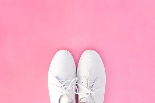 Sneakers bianche su sfondo rosa. vista dall'alto. copyspace.