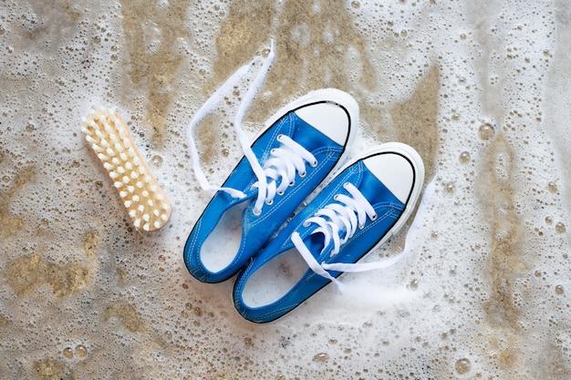 Sneakers con schiuma di detergente in polvere per dissoluzione dell'acqua e spazzola di legno sul pavimento di cemento. lavare le scarpe sporche.