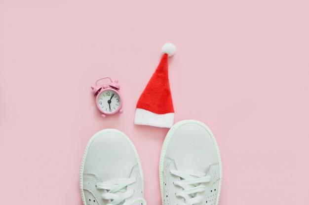 Sneakers da donna bianche, orologio e cappello di babbo natale. il concetto di capodanno, natale. concetto di fitness. vista dall'alto. disteso.