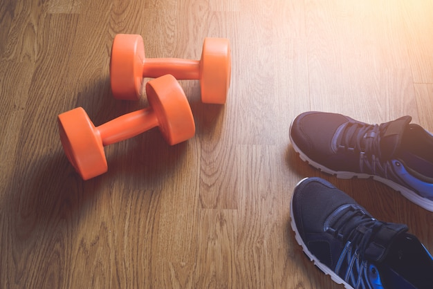Sneakers e manubri fitness su legno