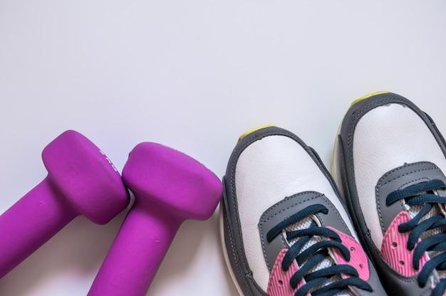 Sneakers e manubri fitness su uno sfondo bianco. strumenti diversi per lo sport. concetto sano stile di vita, sport e dieta. equipaggiamento sportivo. copia spazio. pianta piatta di accessori fitness e allenamento