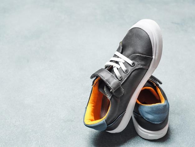 Sneakers grigie e gialle su sfondo grigio
